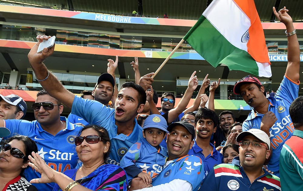 Indian fans wave flags and cheer their team during their Cricket World Cup quarterfinal match against Bangladesh in Melbourne, Australia.