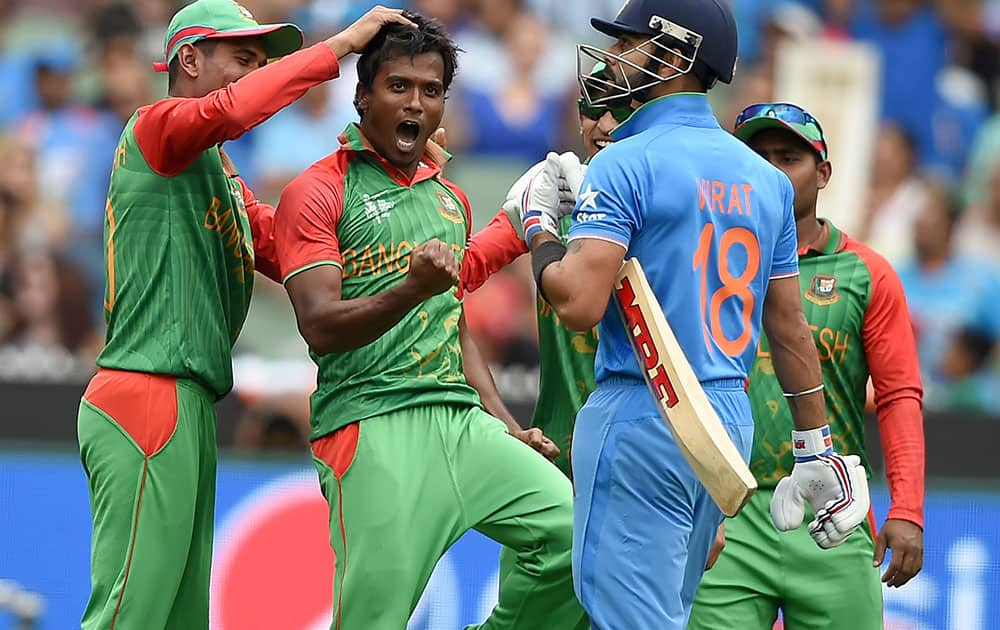 Bangladesh's Rubel Hossain, second left, celebrates with teammate Mahmudullah, left, and Nasir Hossain after taking the wicket of India's Virat Kohli, right, during their Cricket World Cup quarterfinal match in Melbourne, Australia