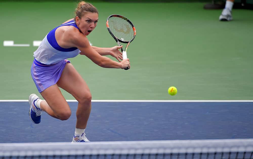 Simona Halep, of Romania, returns to Carla Suarez Navarro, of Spain, during their match at the BNP Paribas Open tennis tournament.