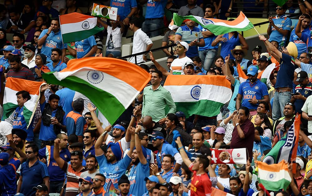 Indian fans wave their flags as they cheer their team during their Cricket World Cup quarterfinal match against Bangladesh in Melbourne, Australia.