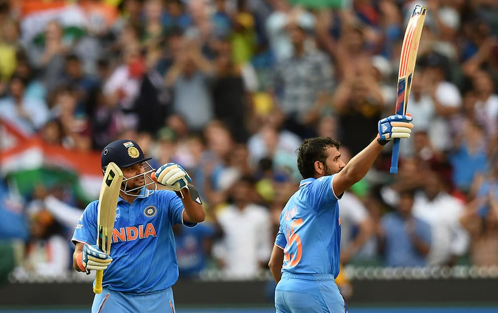 Rohit Sharma, celebrates after scoring a century while batting against Bangladesh as teammate Suresh Raina watches during their Cricket World Cup quarterfinal match in Melbourne, Australia.