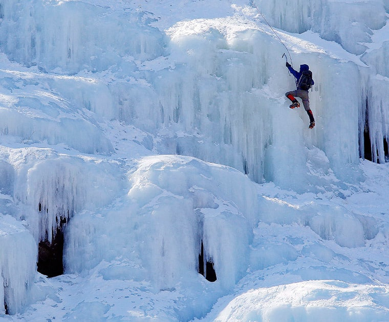An ice climber makes their way up Frankenstein Cliff as freezing temperatures remain on the last full day of winter, in Harts Location.