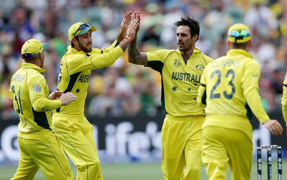 Australia's Mitchell Johnson, is congratulated by teammates after taking the wicket of Pakistan's Haris Sohail during their Cricket World Cup quarterfinal match in Adelaide.