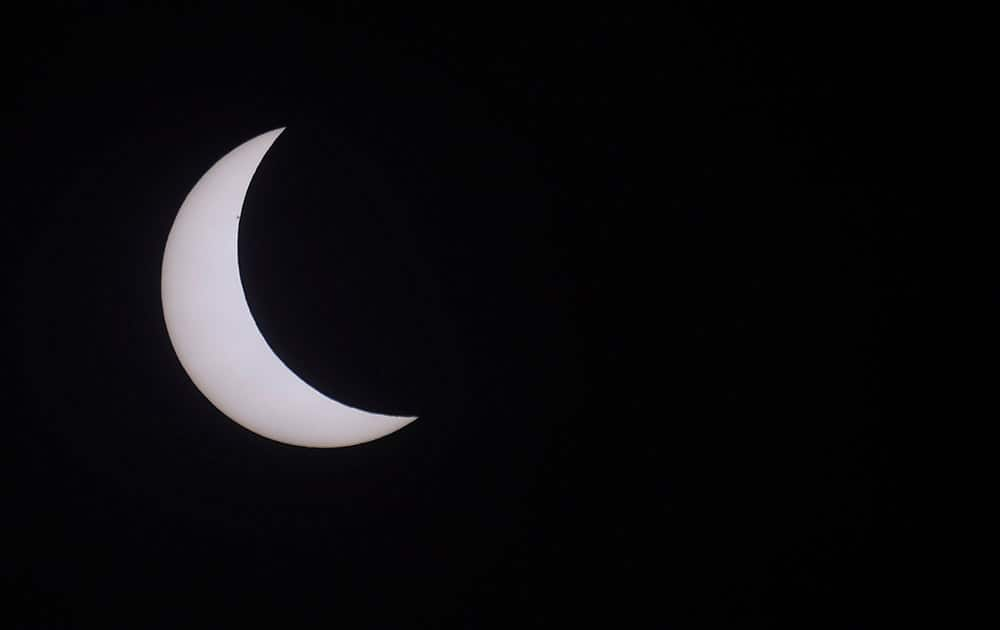 The moon blocks part of the sun during a solar eclipse seen in Northumberland, England.