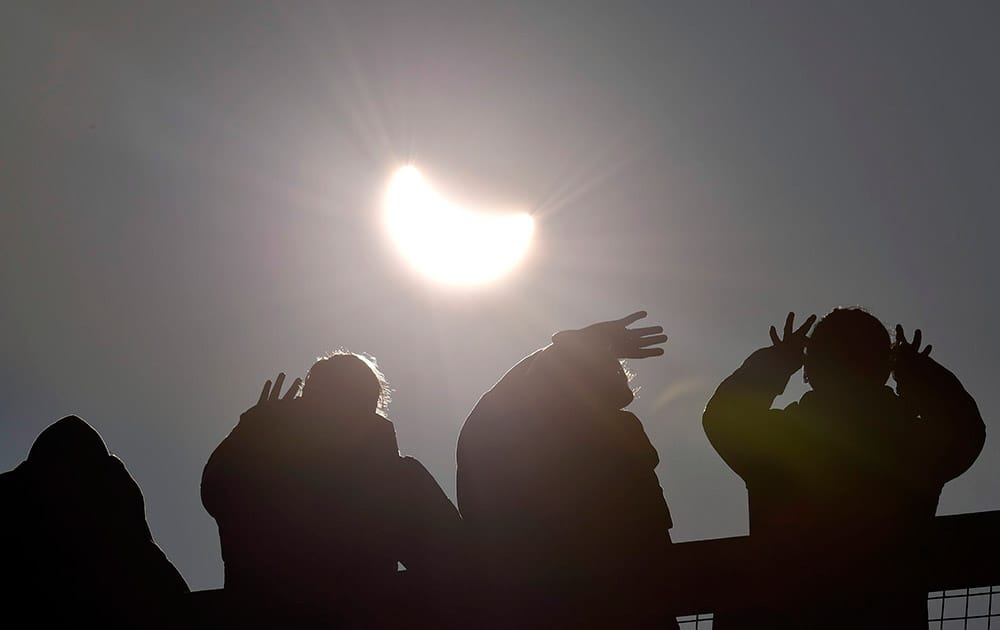 People watch as a solar eclipse begins over the Eden Project near St Austell in Cornwall, England.