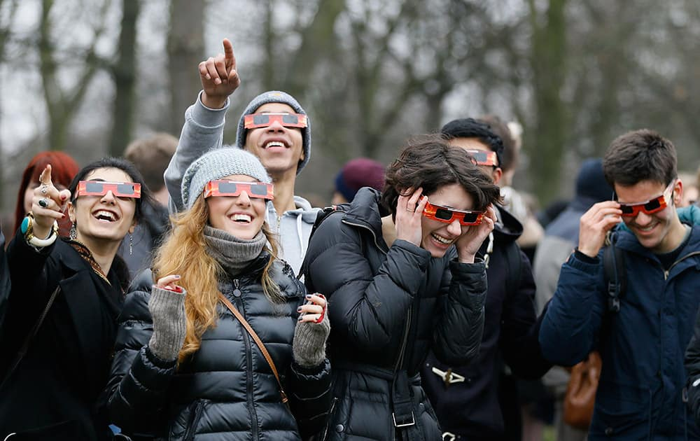 Visitors try on their solar glasses in preparation to view the solar eclipse in Regent's Park in London.