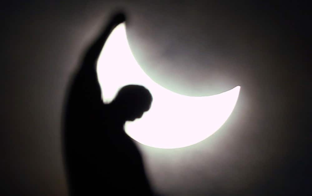 The moon starts to block the sun during a solar eclipse over a statue of the Duomo gothic cathedral in Milan, Italy.
