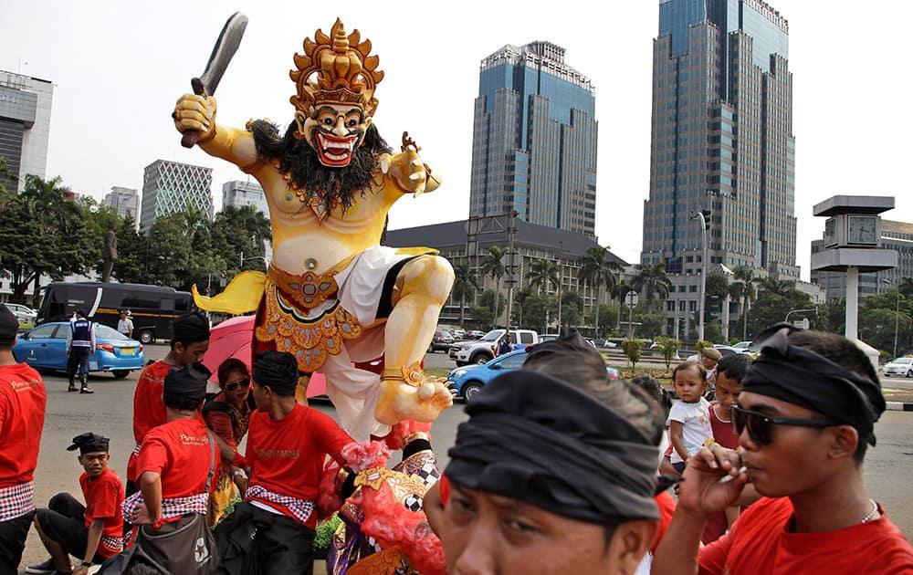 Hindu men take a break near a giant effigy called