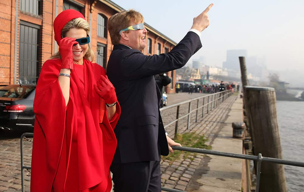 Queen Maxima and King Willem-Alexander of the Netherlands watch the solar eclipse through special glasses at the Fish Market in Hamburg, Germany.