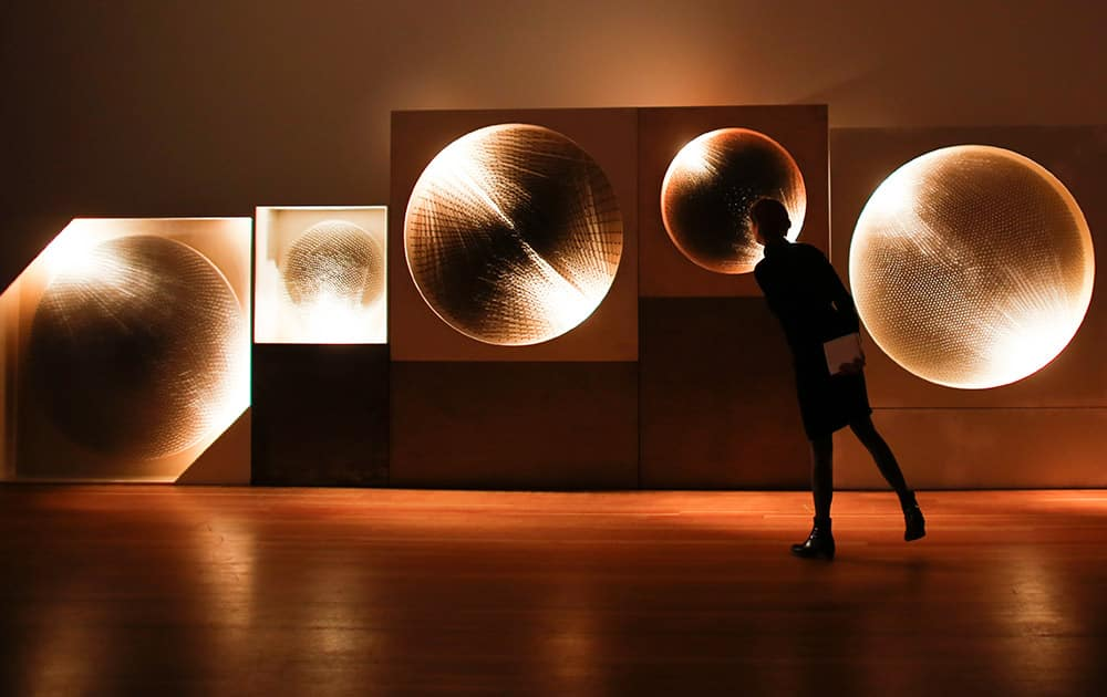A women looks at the art piece 'Cosmic Visions / Light Disks' by German artist Guenther Uecker as part of the ZERO exhibition in Berlin.