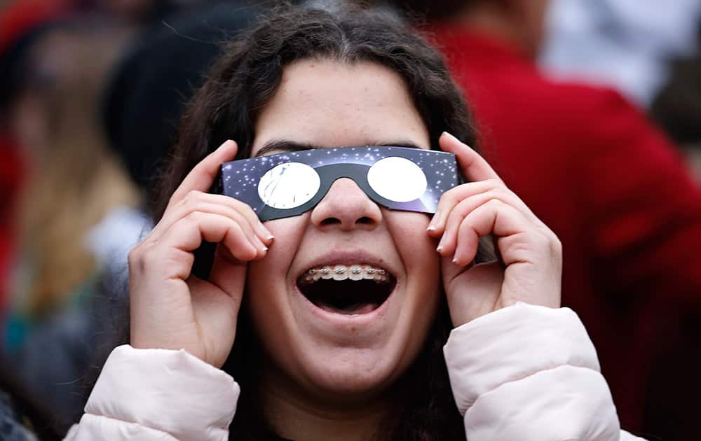 A young girl follows the solar eclipse, viewed through special glasses from the planetarium in Copenhagen.