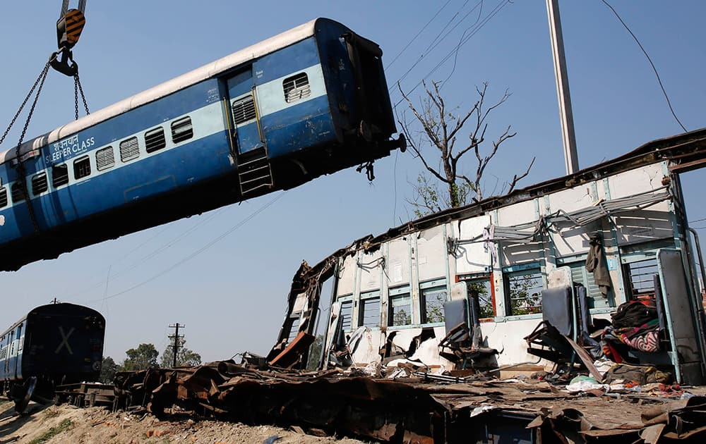 A train compartment is lifted by a crane as the mangled remains of another compartment stands at the site of an accident near Bachhrawan village in Uttar Pradesh.