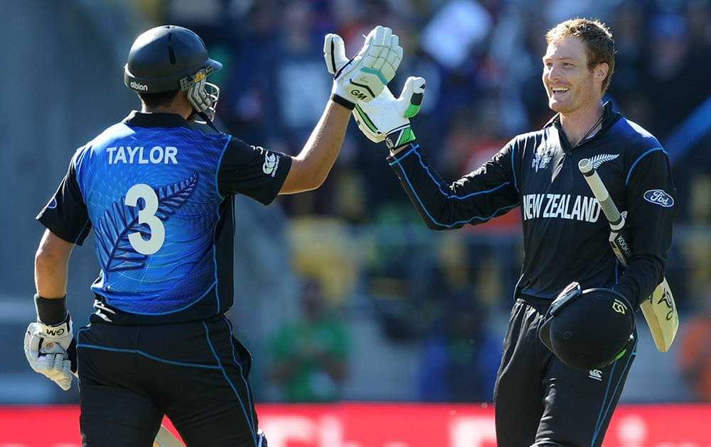 New Zealand's Martin Guptill celebrates with his partner Ross Taylor, left, after scoring a century while batting against the West Indies during their Cricket World Cup quarterfinal match in Wellington, New Zealand.