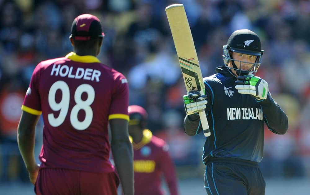 New Zealand's Martin Guptill waves his bat as he celebrates scoring 50 runs as West Indies Jason Holder watches during their Cricket World Cup quarterfinal match in Wellington.