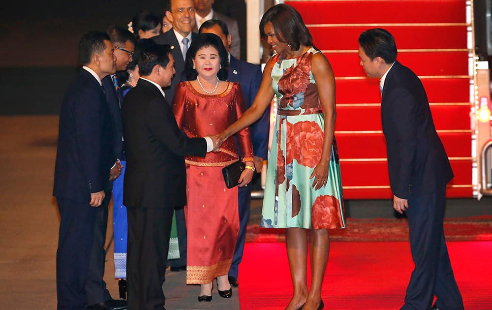 US first lady Michelle Obama is accompanied by Bun Rany, the first lady of Cambodia, as she greets a government official upon arrival at Siem Reap International Airport, in Siem Reap, Cambodia. Mrs. Obama's Friday evening arrival in Cambodia comes after a three-day visit to Japan.