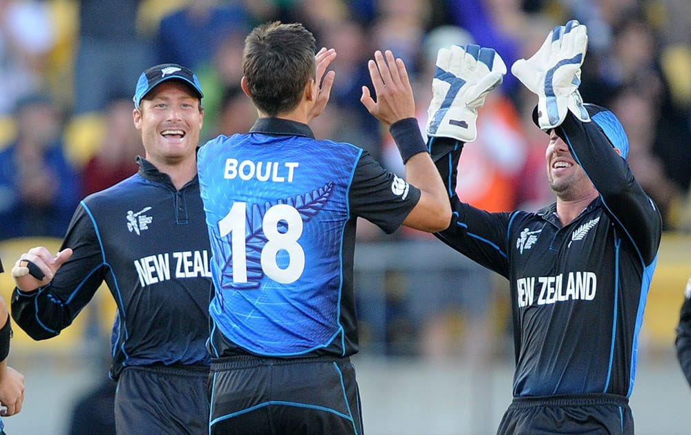 New Zealand's Trent Boult is congratulated by teammates Martin Guptill and Luke Ronchi, right, after bowling West Indies batsman Johnson Charles during their Cricket World Cup quarterfinal match in Wellington, New Zealand.
