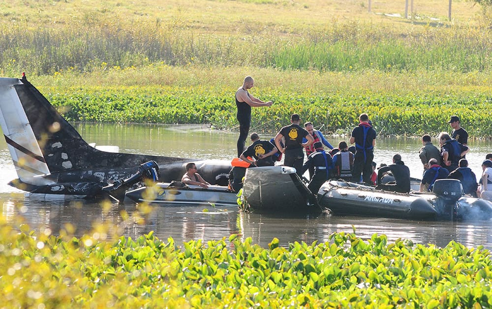 Rescue personnel work to recover remains from the wreckage of a crashed aircraft at Laguna del Sauce.
