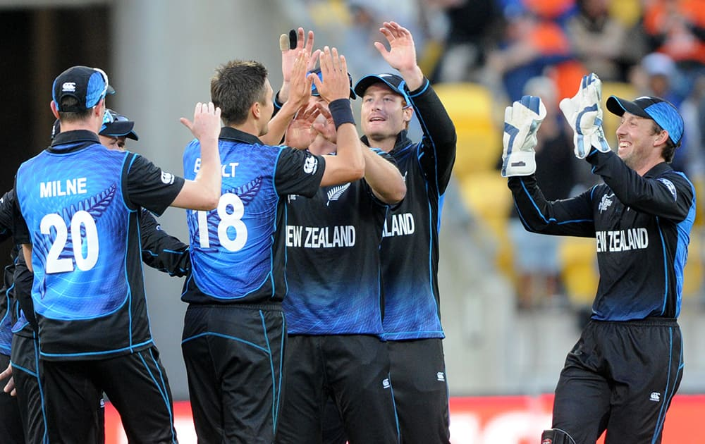 New Zealand's Trent Boult, is congratulated by teammates after the dismissal of West Indies Denesh Ramdin during their Cricket World Cup quarterfinal match in Wellington.