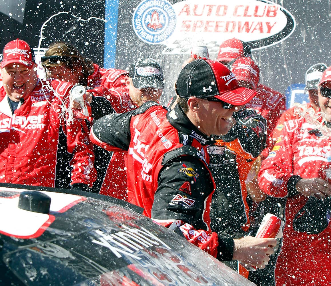 Kevin Harvick gets drenched by his team after winning the NASCAR Xfinity Sprint Cup Series auto race in Fontana, Calif.