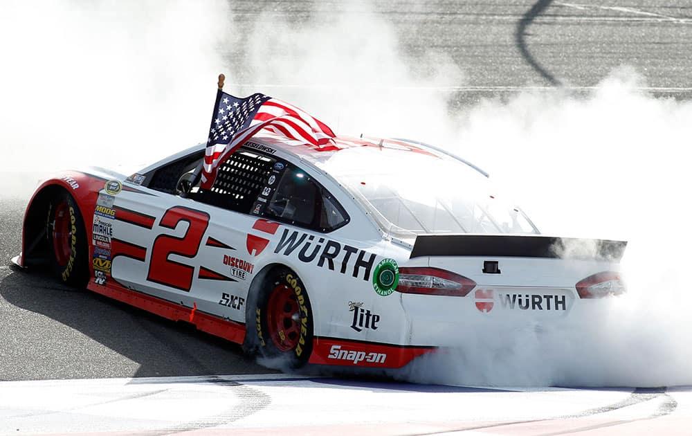 Brad Keselowski celebrates after winning the NASCAR Sprint Cup Series auto race in Fontana, Calif.