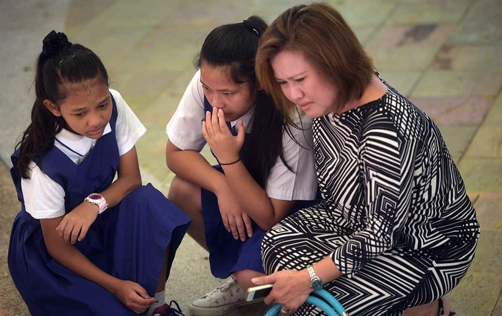 Sophia Amelia Norhisam, 11, left, Sarah Allysah Norhisam, 14, grieve with their mother Roslina A. Majid, 46, at a hospital where Singapore's founding prime minister Lee Yuan Yew passed away on Monday, March 23, 2015 in Singapore.