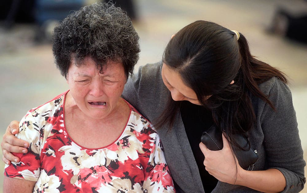 A woman is comforted by hospital staff as she cries at Singapore General Hospital where former prime minister Lee Kuan Yew passed away in Singapore, Monday, March 23, 2015.