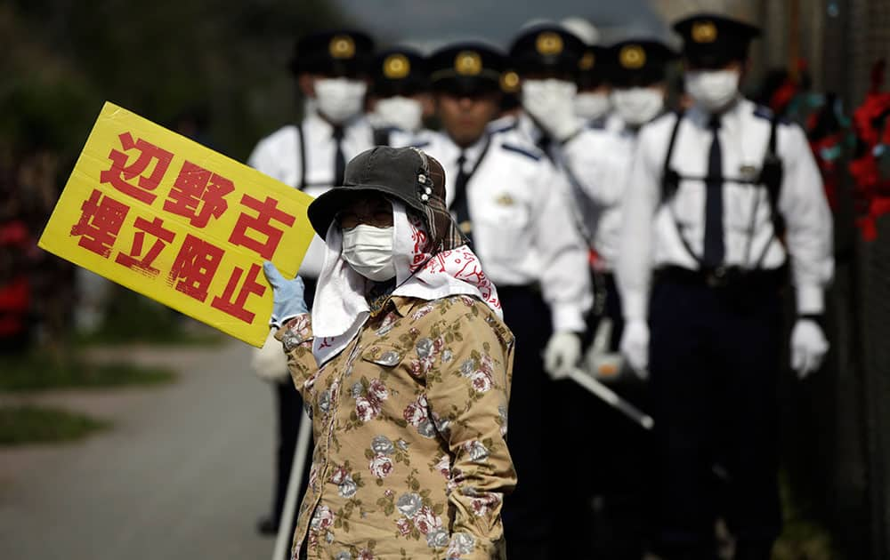 Japanese police officers stand guard as a protester against the relocation of U.S. Marine Corps Air Station Futenma, as protesters stage a rally outside Camp Schwab, an American base near a planned relocation site, in Nago, Okinawa Prefecture.