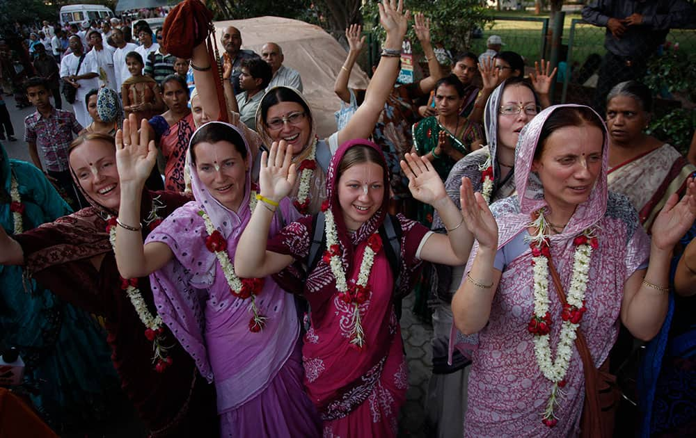 Foreign devotees chant hymns during a chariot procession of Lord Jagannath ahead of Hindu Festival Ram Navami in Ahmadabad, India.