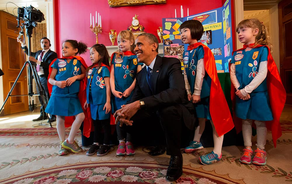 President Barack Obama poses with six-year-old Girl Scouts from Tulsa, Okla. during the White House Science Fair, in the Red Room of the White House in Washington.