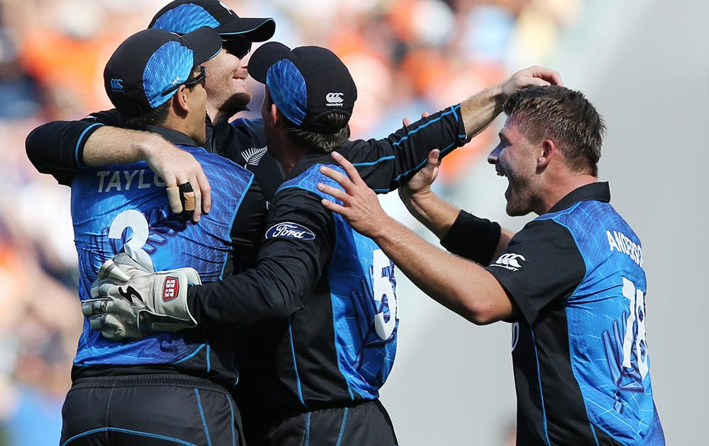 New Zealand's Martin Guptill, second left, is congratulated by teammates after taking a catch to dismiss South Africa's Rilee Rossouw during their Cricket World Cup semifinal in Auckland, New Zealand.