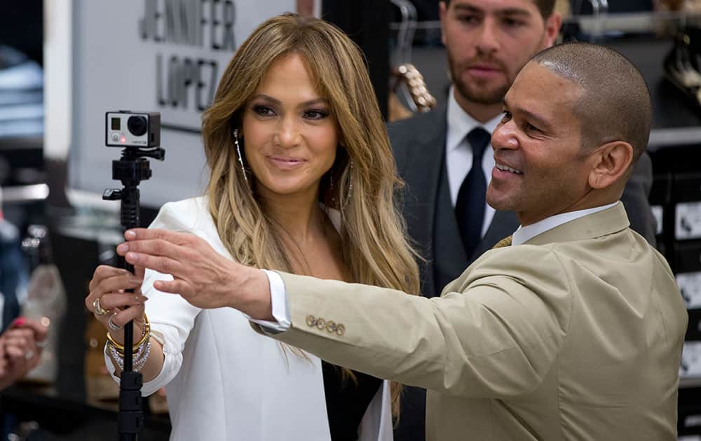 Jennifer Lopez, left, records a video during an event launching her clothing and accessories collection at a store in Mexico City.