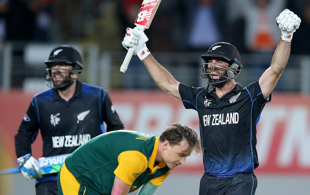 New Zealand's Grant Elliott raises his arms in celebration with teammate Dan Vettori,as South Africa's Dale Steyn reacts after they defeated South Africa by four wickets in their Cricket World Cup semifinal in Auckland.