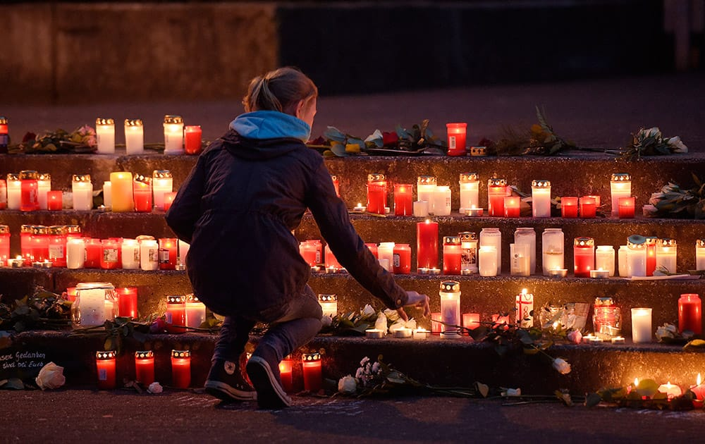 A school girl lights a candle in front of the Joseph-Koenig Gymnasium in Haltern, western Germany.