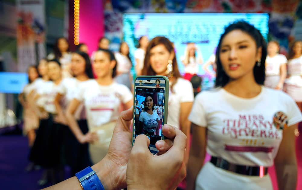 A person takes a photo of the contestants in a Thai transvestite beauty pageant at a shopping mall in Bangkok, Thailand .The final round of 60 contestants will be held in May in the seaside resort city of Pattaya.