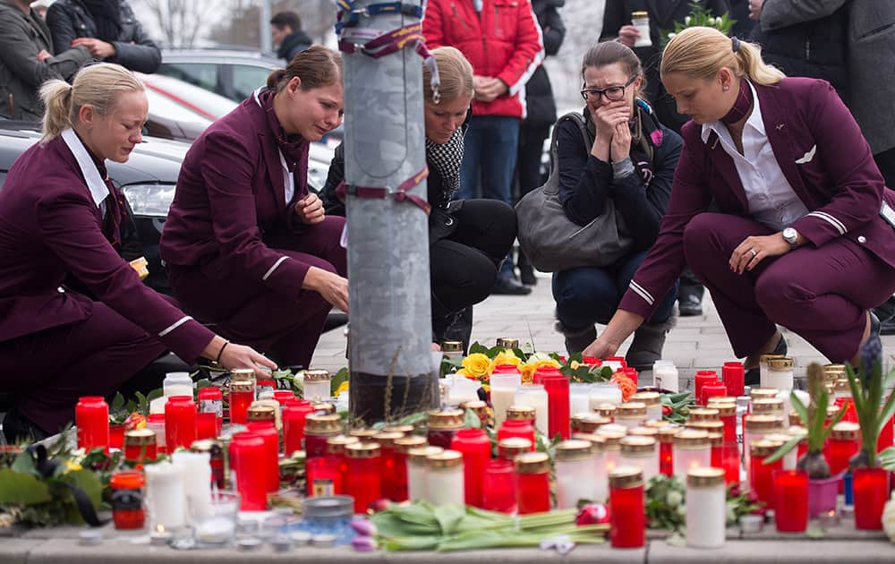 Employees of Germanwings place candles and flowers as they mourn in front of the company's headquarters in Cologne, the day after a Germanwings aircraft , carrying 150 people, crashed in France on the way from Barcelona, Spain, to Duesseldorf, Germany.