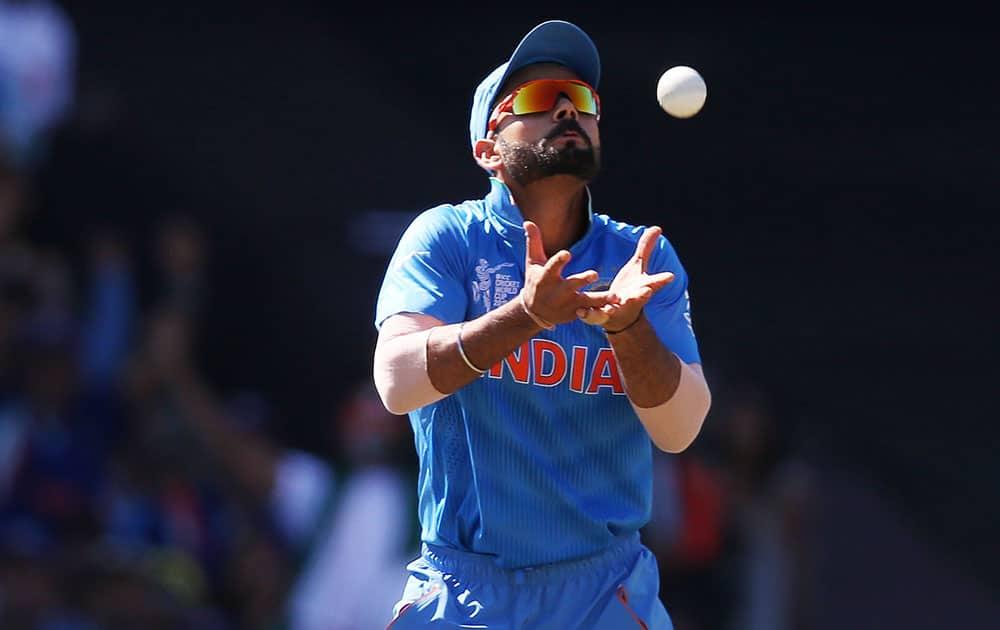 India's Virat Kohli takes a catch to dismiss Australia's David Warner during their Cricket World Cup semifinal in Sydney, Australia.