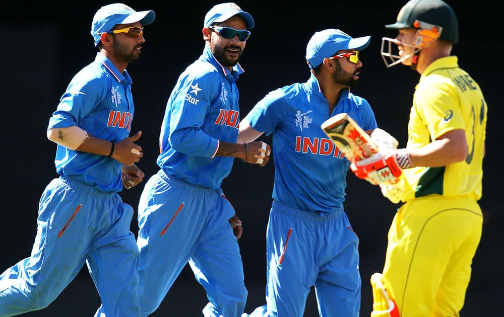 Indian players celebrate after dismissing Australian batsman David Warner, right, during their Cricket World Cup semifinal in Sydney, Australia.
