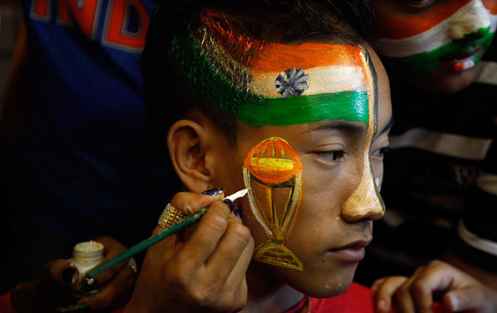 Cricket fan gets his face painted in the colors of the national flag to cheer for the Indian cricket team ahead of the ICC Cricket World Cup semifinal match against Australia, in Ahmedabad,