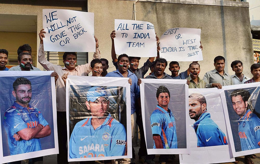 Cricket fans hold the poster of Indian Cricket players wishing them for their World Cup semi final clash against Australia to be held in Sydney, in Bengaluru.