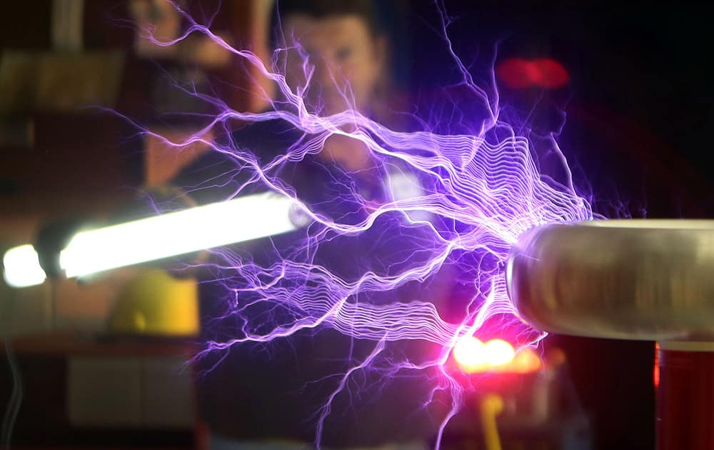 Instructor Robert Callier lights up a bulb with a Tesla coil that he built with students at Haney Technical School, in Panama City, Fla.