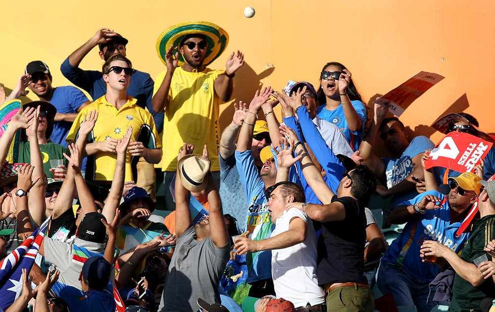 Spectators attempt to catch a ball hit by Australia's Glenn Maxwell during their Cricket World Cup semifinal against India in Sydney, Australia.