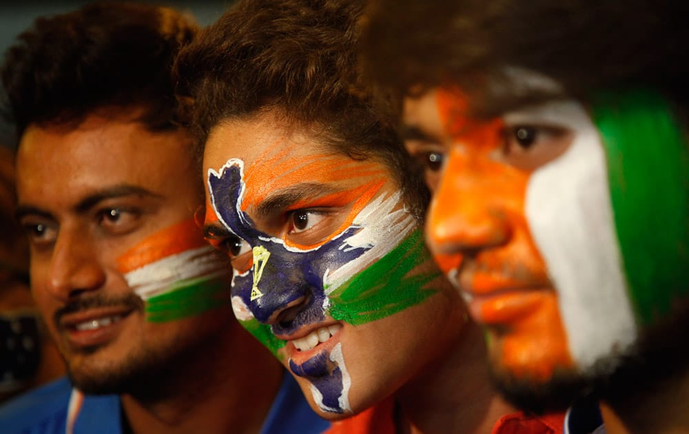 Indian cricket fans stand with their faces painted in the colors of the national flag to cheer for the Indian cricket team ahead of the ICC Cricket World Cup semifinal match against Australia, in Ahmadabad.