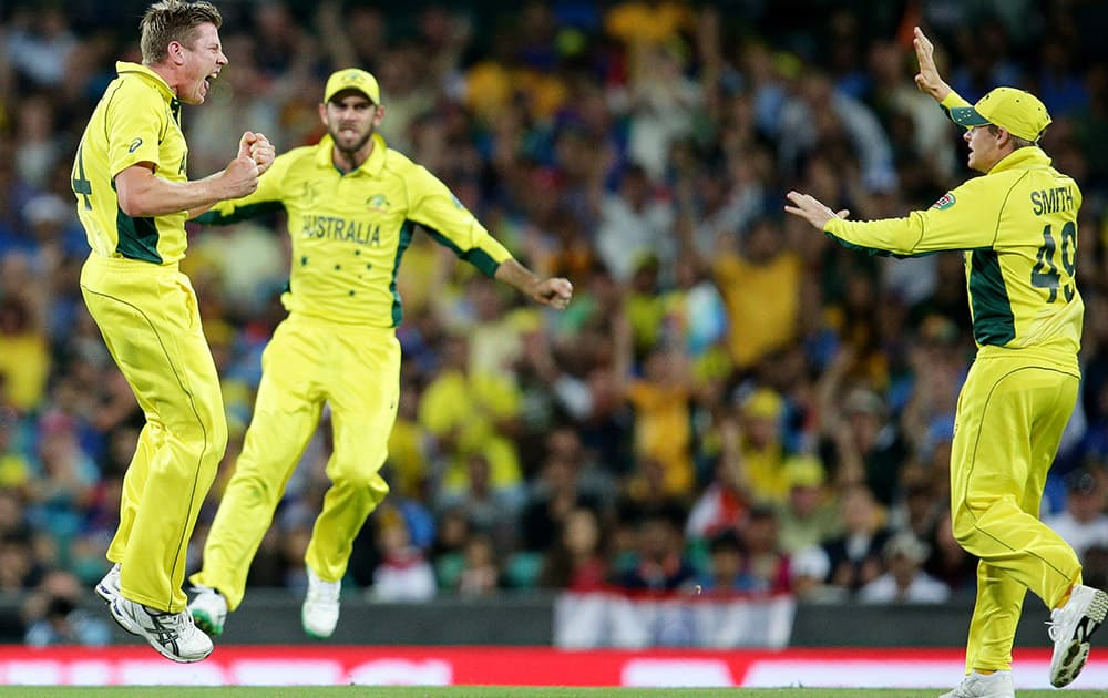 Australia's James Faulkner celebrates with teammates Australia's Steve Smith and Glenn Maxwell after taking the wicket of India's Suresh Raina during their Cricket World Cup semifinal in Sydney, Australia.