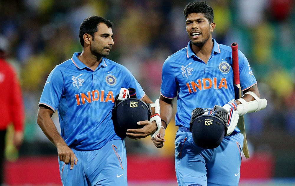 Umesh Yadav and Mohammed Shami walk from the field after their 95 run loss to Australia in their Cricket World Cup semifinal in Sydney, Australia.