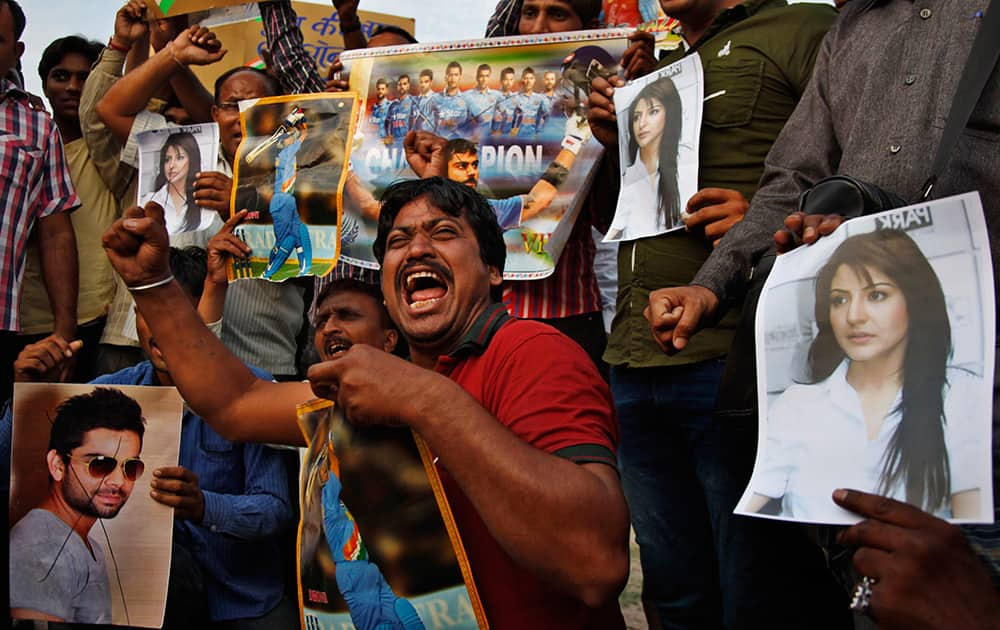 Fans shout slogans with posters of Virat Kohli and his girlfriend and Bollywood actor Anushka Sharma, as they react to India's defeat in the ICC cricket world cup semi-final match against Australia, in Ahmadabad.