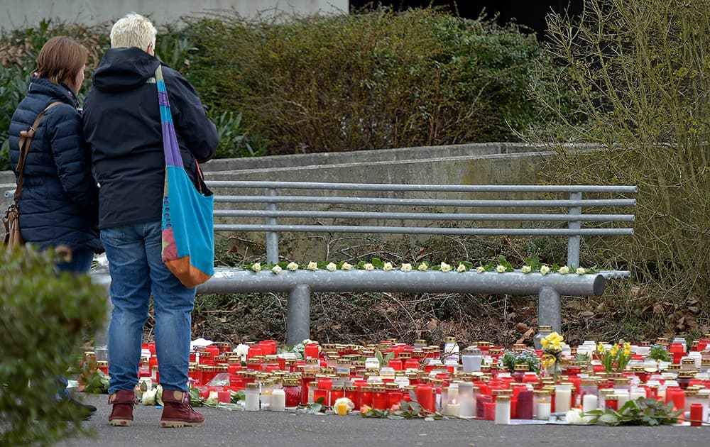People look at flowers and candles placed in front of the Joseph-Koenig Gymnasium in Haltern, Germany.