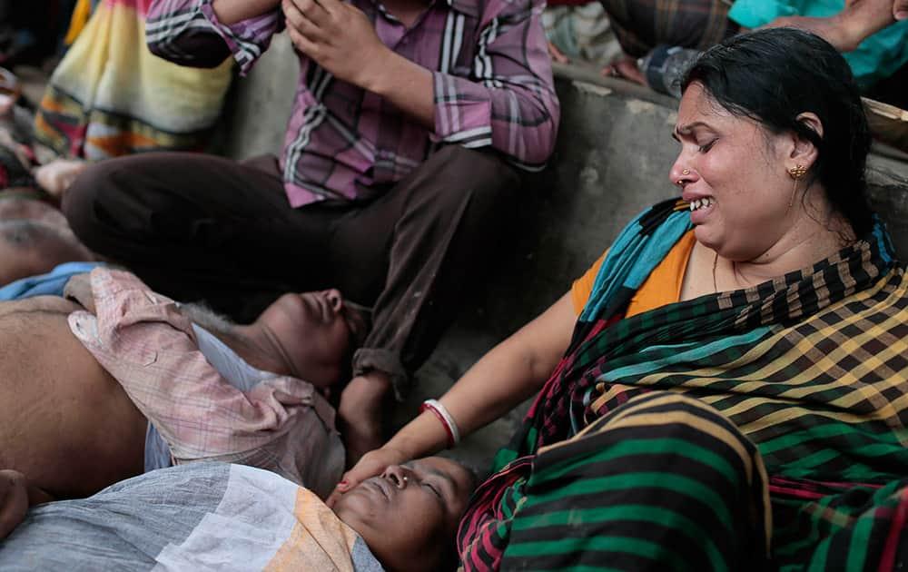 A Bangladeshi Hindu devotee Sapna Das cries as she holds the body of a relative who was killed in a stampede in Langalbandh, 20 kilometers (12 miles) southeast of capital Dhaka, Bangladesh.