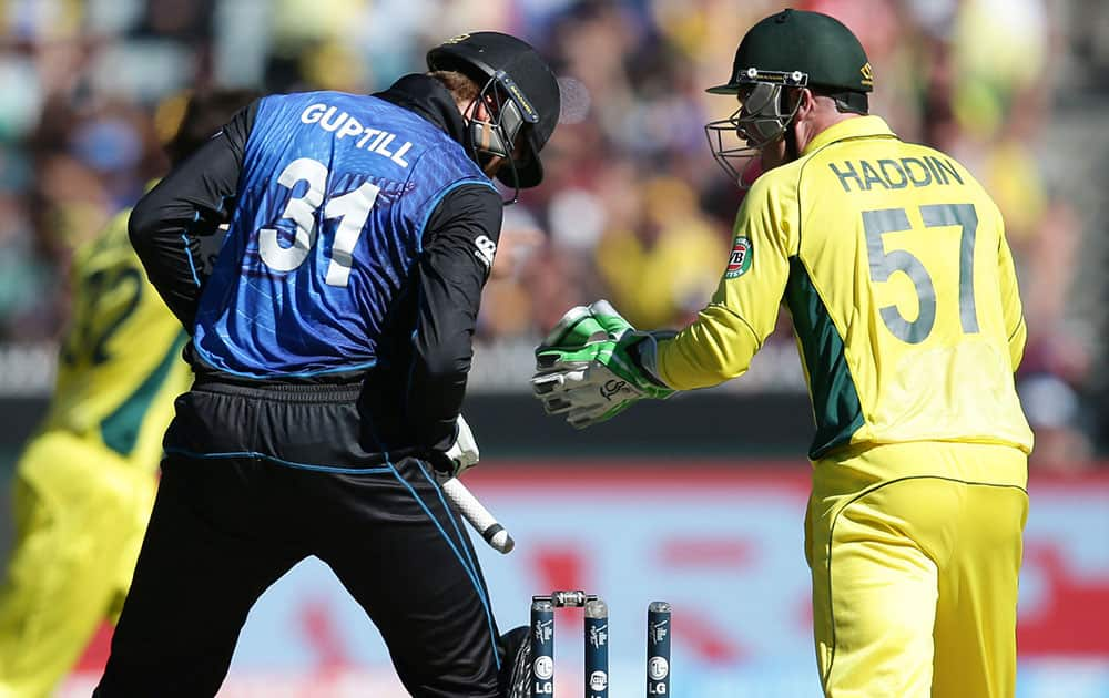 New Zealand's Martin Guptill, left, looks down after he was bowled as Australia's wicketkeeper Brad Haddin celebrates during the Cricket World Cup final in Melbourne, Australia.
