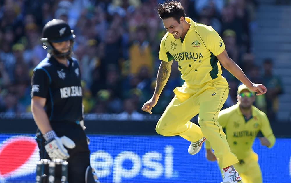 Australia's Mitchell Johnson, right, celebrates after taking the wicket of New Zealand's Kane Williamson, left, during the Cricket World Cup final in Melbourne, Australia.