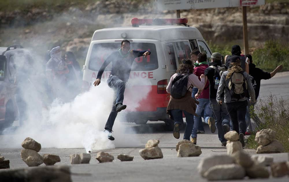 A Palestinian demonstrator kicks a tear gas canister towards Israeli soldiers as activists run away from the gas during a protest marking Land Day, in the West Bank village of Nabi Saleh near Ramallah.
